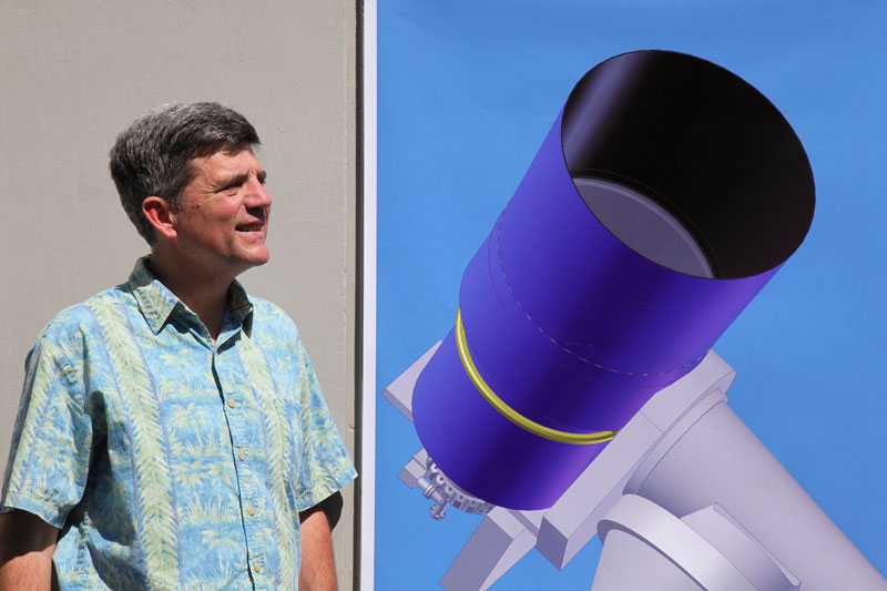 [ATLAS Principal Investigator Dr. John Tonry and a correctly sized image of one of the telescope designs. Image credit: Louise Good, University of Hawaii Institute for Astronomy.]